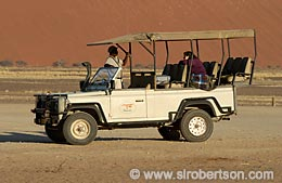 All terrain vehicle, safari truck, Landrover with driver and woman, Sossusvlei, Namib Desert, Namibia