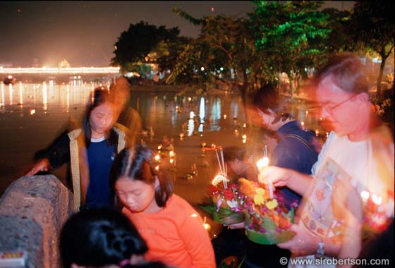 Photo: Lighting Candles on Krathong Boats