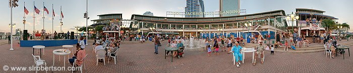 Crowd of people listen to jazz band play at the Jacksonville Landing on the St. Johns River, Jacksonville, Florida