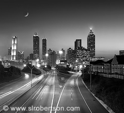 Atlanta skyline at night with highway, light streaks from traffic, cars, cresent moon, skyscrapers